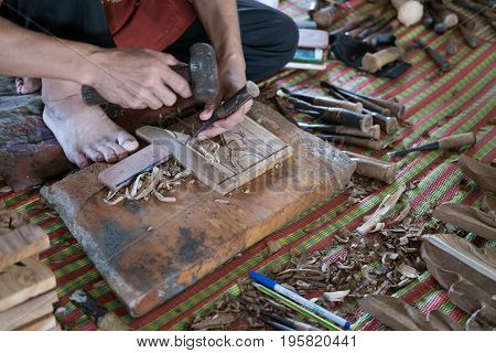CHIANG MAI, THAILAND - JULY 1: craftsman use a gouge to carve traditional bas-relief on wood at Lanna Expo 2017 in Chiang Mai Thailand on July 1 2017.