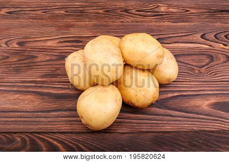 Uncooked, raw and fresh potatoes on a dark brown wooden background. Summer harvest of new potato tubers. Nutritious organic potatoes. Organic and uncooked new light brown potatoes. Fresh vegetables.