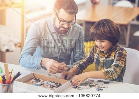Where to put it. Positive nice delighted man holding a jigsaw puzzle piece and helping his son so do the puzzle while spending time together with him