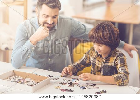 Brain development. Nice intelligent delighted kid sitting with his father and doing a jigsaw puzzle while having fun
