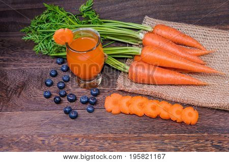 Healthy eating and dieting conceptfresh carrot and carrot juice or organic healthy juice in glass fruitvegetables on a grey wooden table wall background with copy space .