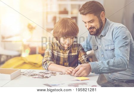 Time together. Nice intelligent positive boy sitting at the table and doing a jigsaw puzzle while being with his father