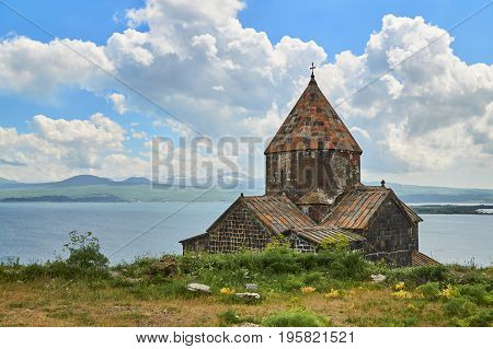 View of an ancient church in armenian monastery Sevanavank with blue lake background