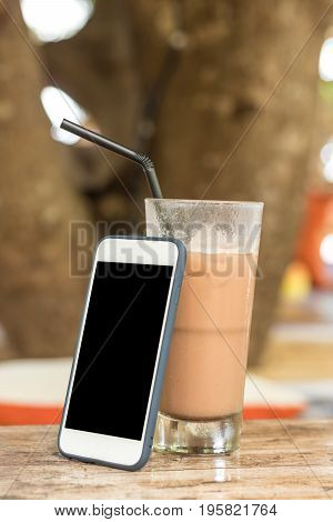 Glass Of Cold Coffee On Wood outside. Smartphone with black screen.