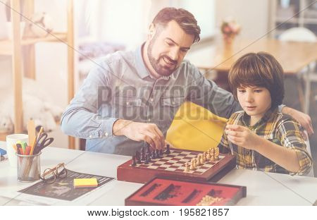Board games. Cute smart curious boy holding a chess piece and putting it on the chessboard while learning how to play chess