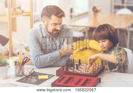 In the middle of the game. Positive nice intelligent father and son sitting opposite each other and playing chess while having a great time together
