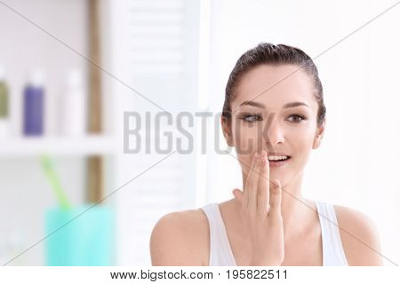 Young woman touching lips in light room