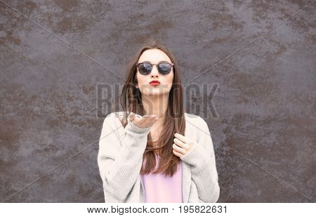 Beautiful young woman with bright lips on textured background