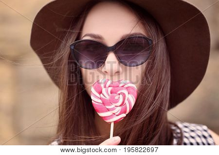 Beautiful young woman hiding lips behind tasty lollipop on blurred background
