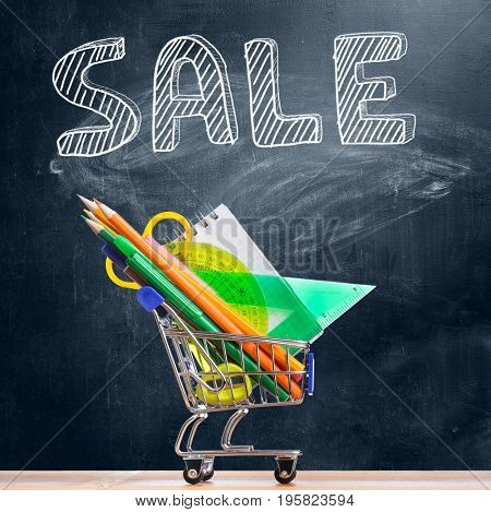 Back to school shopping cart. Accessories in trolley against chalkboard with Sale caption