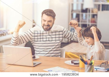 Our team has won. Delighted happy positive father and son holding hands up and being happy for their team while watching football online