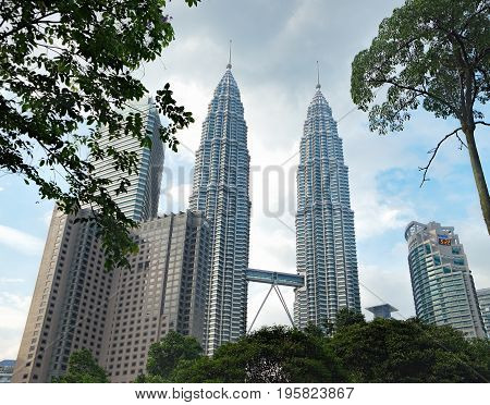 Kuala Lumpur, Malaysia - February 10 2016: Petronas Towers is the most popular tourist destination in Malaysian capital. Urban landscape with modern skyscrapers and the tropical nature