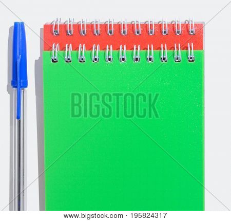 Green and red notepads with pen on table top view