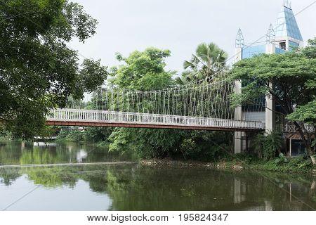 View Of Pedestrian Suspension Bridge Or Steel Hanging Footbridge Above The Lake