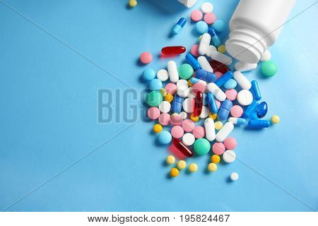 Plastic container and different pills on color background