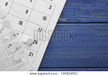 Plastic container with pills and paper calendar on wooden table