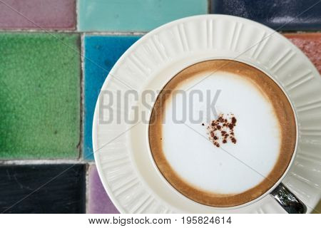 Hot Cappuccino Coffee Drink On Colorful Tile. Top View