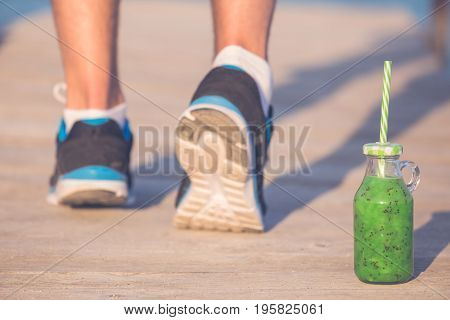 Close up of runner in running shoes and kiwi smoothie. Close up on feet. Fitness and healthy eating concepts.