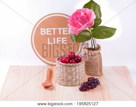 Cherries and wooden spoon with dark grapes inspiration words flower and white background.