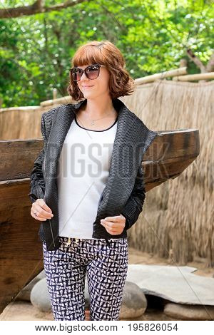 Portrait of young stylish beautiful woman in black snakeskin python jacket and sunglasses, fashion outfit, autumn trend, accessories, close-up. Near the boat.