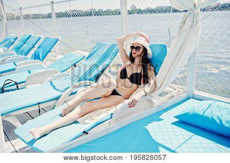 Portrait Of A Beautiful Girl Wearing Black Bikini Swimsuit, White Hat And Sunglasses Laying On The L