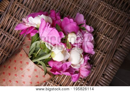 Beautiful bouquet with fragrant peonies on wicker surface