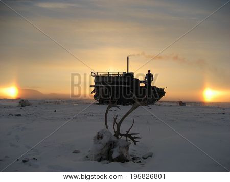 Taimyr. Winter tundra. Hunting for the reindeer. Cross-country vehicle and two suns.