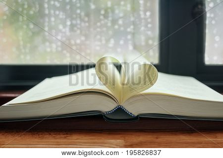 Old open book with pages shaped like heart