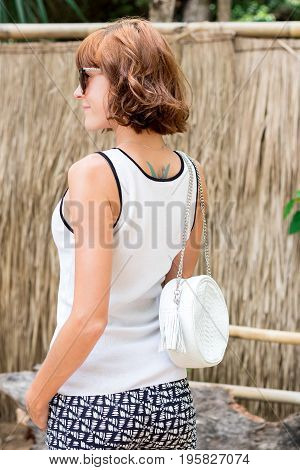 Elegant outfit. Closeup of leather bag in hands of stylish woman. Portrait og Fashionable girl. Female fashion.