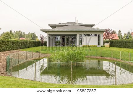 House exterior in the suburbs with pond