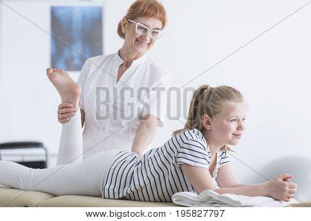 Physiotherapist Stretching Girl's Leg
