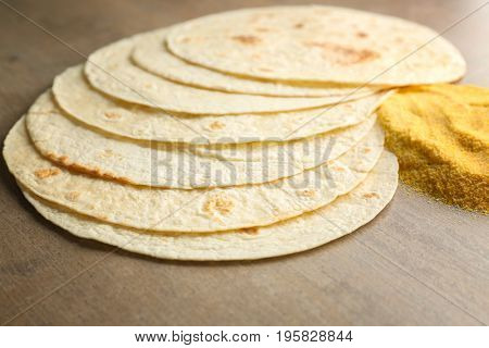 Composition with unleavened tortillas and corn flour on grey background
