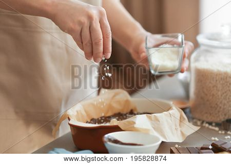 Woman sprinkling desiccated coconut into baking dish with delicious rice dessert on table
