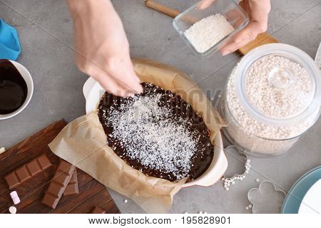 Woman sprinkling desiccated coconut onto rice dessert in baking dish on table