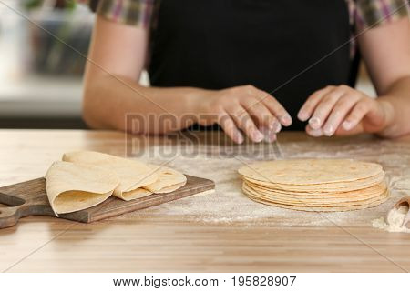 Chef cooking delicious unleavened tortillas on wooden table