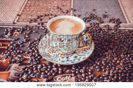 Cup of morning fresh fragrant coffee on a table with grains