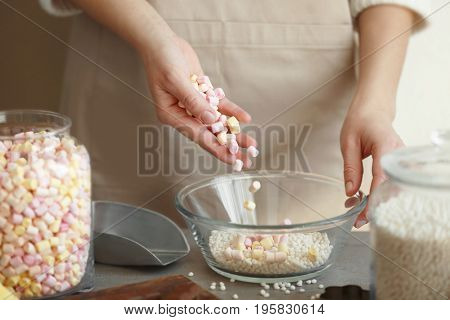 Woman adding marshmallow into glass bowl with crispy rice balls on table