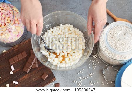 Woman mixing ingredients for rice dessert in glass bowl on table