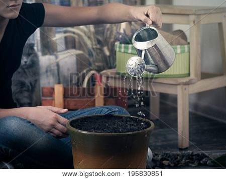 Girl watering from a watering can flower pot. Hobby people - indoor gardening