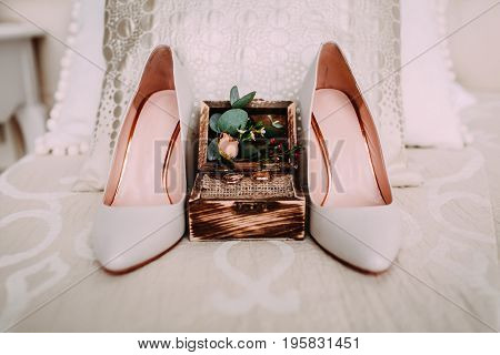 Rustic wooden box with gold wedding rings and flowers stand next to elegant bridal shoes. Morning preparation