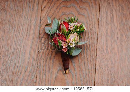 Boutonniere groom on a wooden background. Close-up. Horisontal