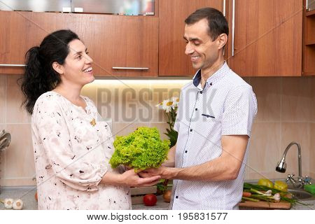 couple in kitchen interior with basket of fresh fruits and vegetables, healthy food concept, pregnant woman and man