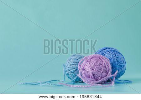 Few Knitting yarn on plain aquamarine background