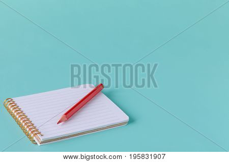 Open Spiral Blank Notebook With Pencil On Blue Paper Background