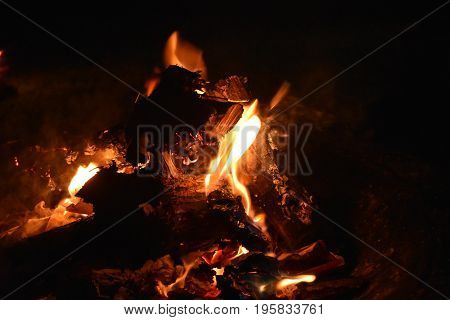 Fire embers and coals with dark logs on black background