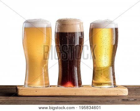 Three glasses of beer on the wooden table.