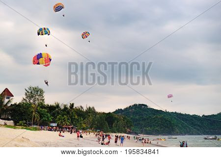 Langkawi, Malaysia - February 13, 2016: Paragliders at sunset summer adventure in Pantai Tengah Beach, Langkawi Island, Malaysia. Unidentified tourists take pictures and watch the colorful sunset.