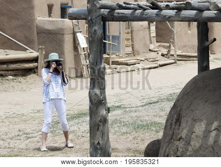 TAOS, NEW MEXICO, JULY 5. The Taos Pueblo on July 5, 2017, near Taos, New Mexico. A Woman Tourist Photographs Details at the North House of the Taos Pueblo near Taos in New Mexico.