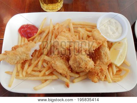 Delicious crispy battered deep fried fish and chips with mayonnaise and ketchup