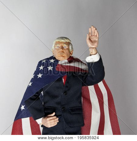 Caricature of US President Donald Trump wearing an American Flag as a cape - using toy action figure